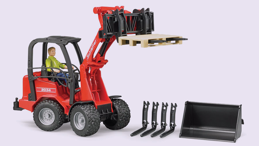 A realistic Bruder Schaffer telehandler toy with driver and various attachments
