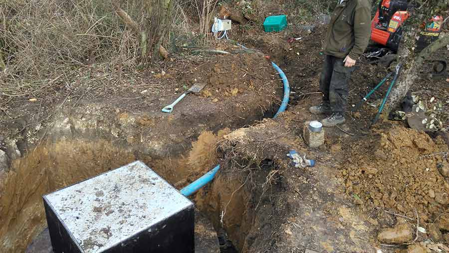 New septic tank installed in the ground with plastic piping in a trench