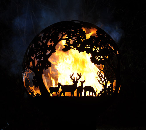 One of Andy Gage's fireballs - a steel fire pit with a deer and trees motif