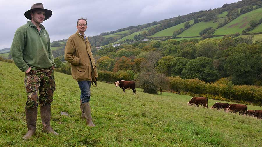 Alex Fraser and Ben Williams stand in an upland pasture