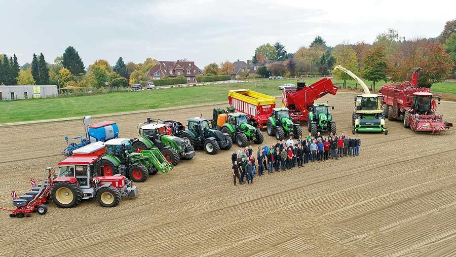 A group of people infront of a long line of assorted farm machinery