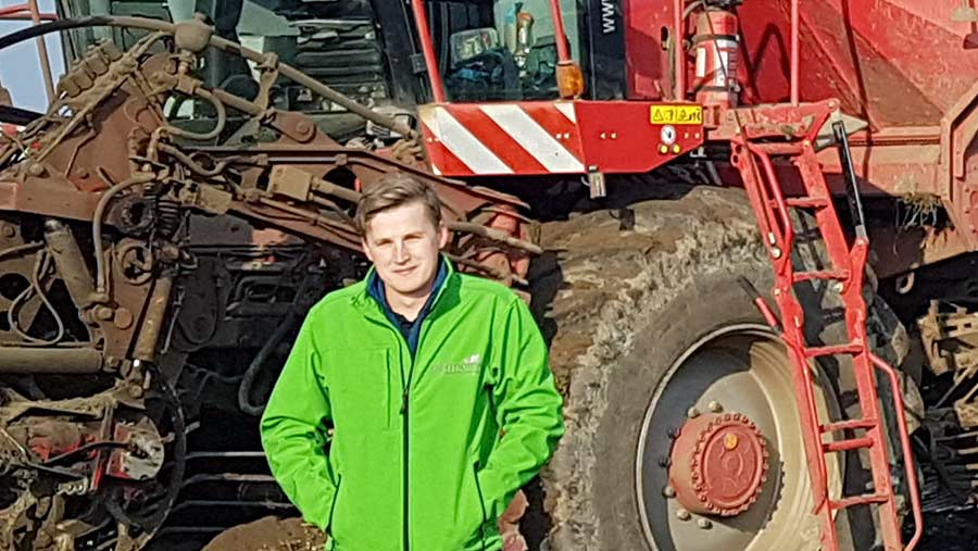 George Palmer stands in front of a sugar beet harvester