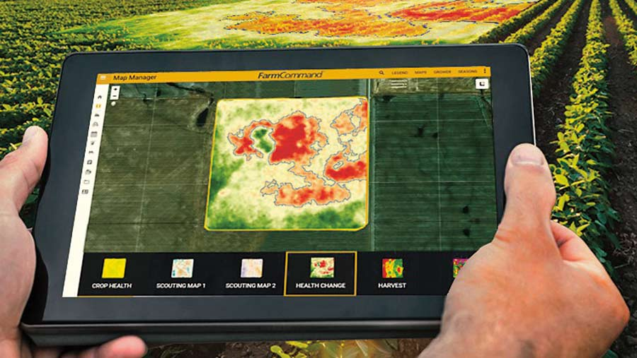 Hands holding a tablet computer with crop data on it