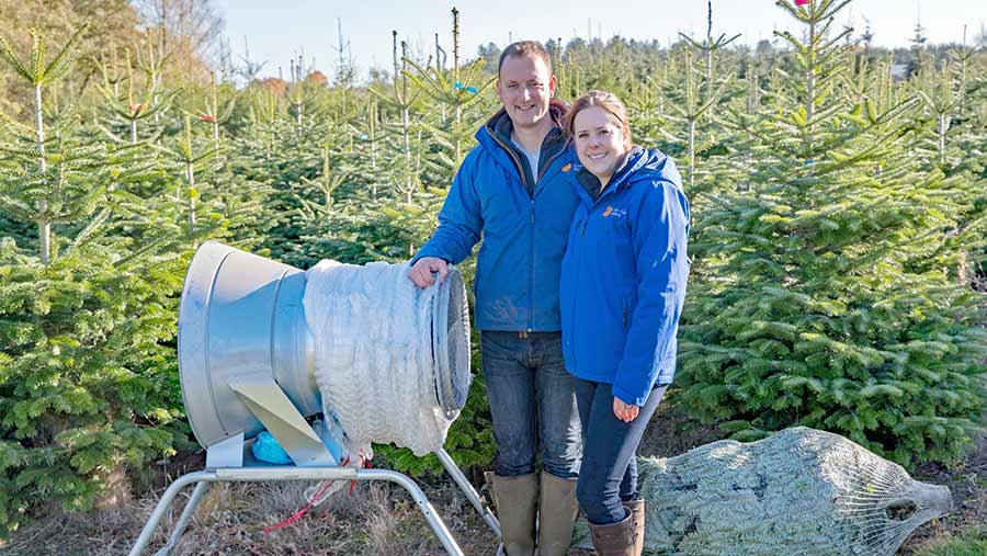 Guy and Emily French in field with Christmas trees