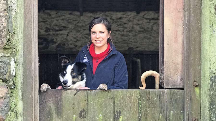 Teleri Fielden with her sheepdog peering out of stable door