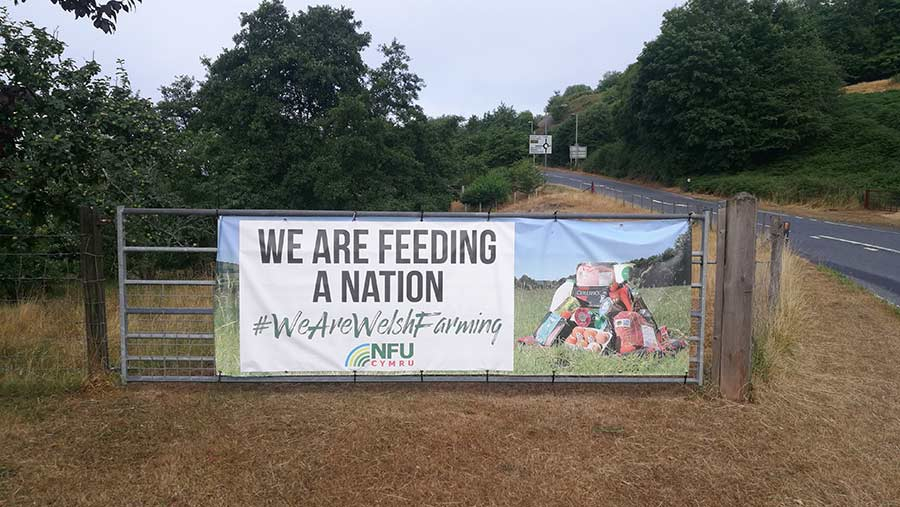 """Poster on a farm gate reads: """"We are feeding a nation. We are Welsh farming"""""""