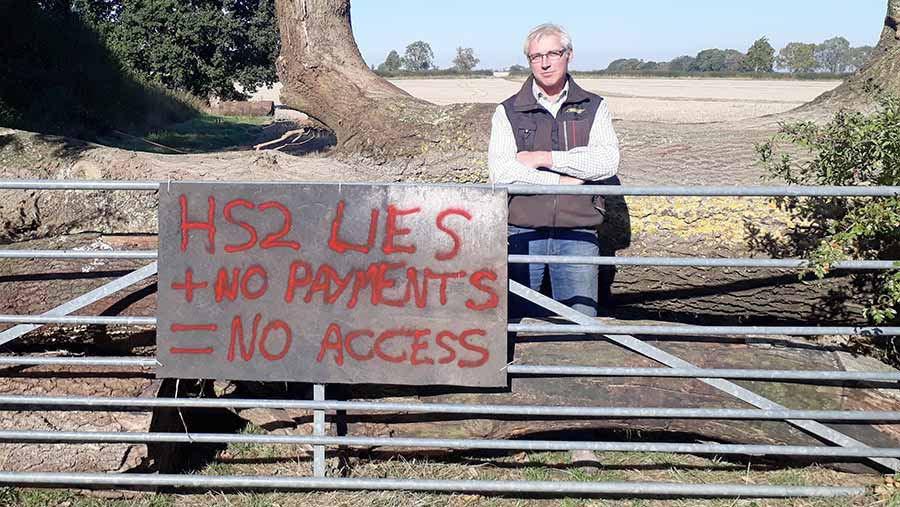 """Sam Burton stands beside a sign that says: """"HS2 lies + no payments = no access"""""""