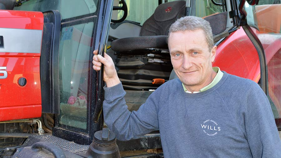 Farmer Marcus Palmer stands at the door of his tractor