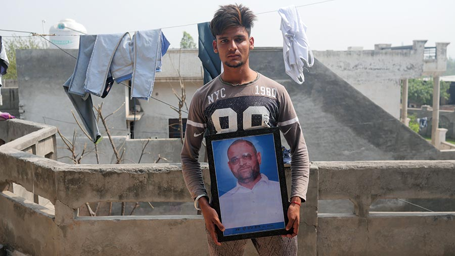 A young Indian man stands with a photograph of his father