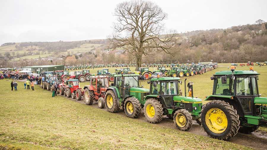A line of tractors winds off into the distance