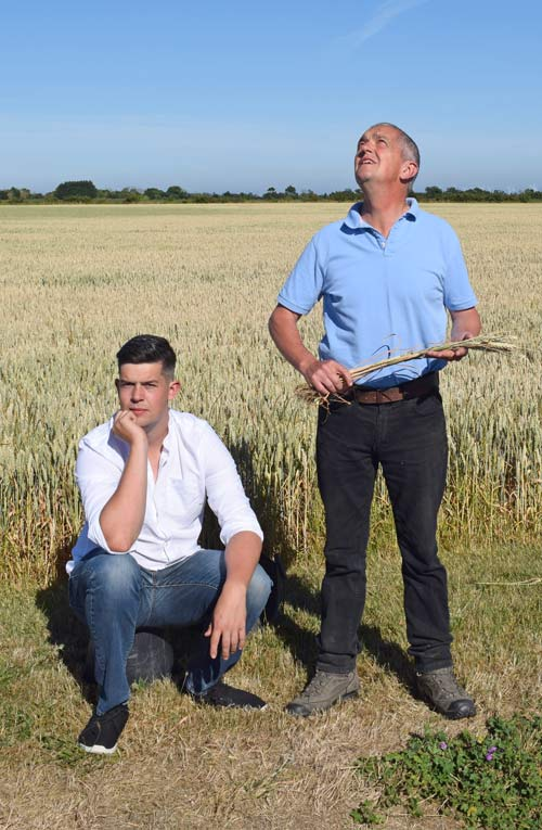 Guy Smith and his son Henry stand in a dry field