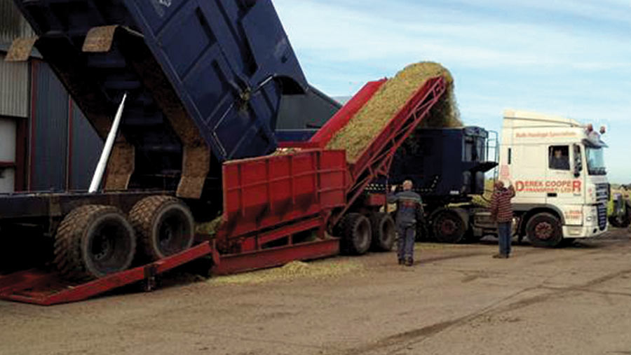 Silage loader in use loading an articulated trailer