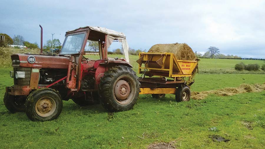 Bale unwinder being pulled by an old MF 165 tractor