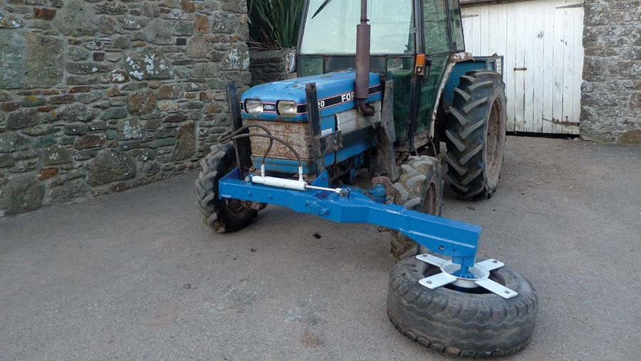 Silage pusher featuring an old wheel and tyre attached to a boom