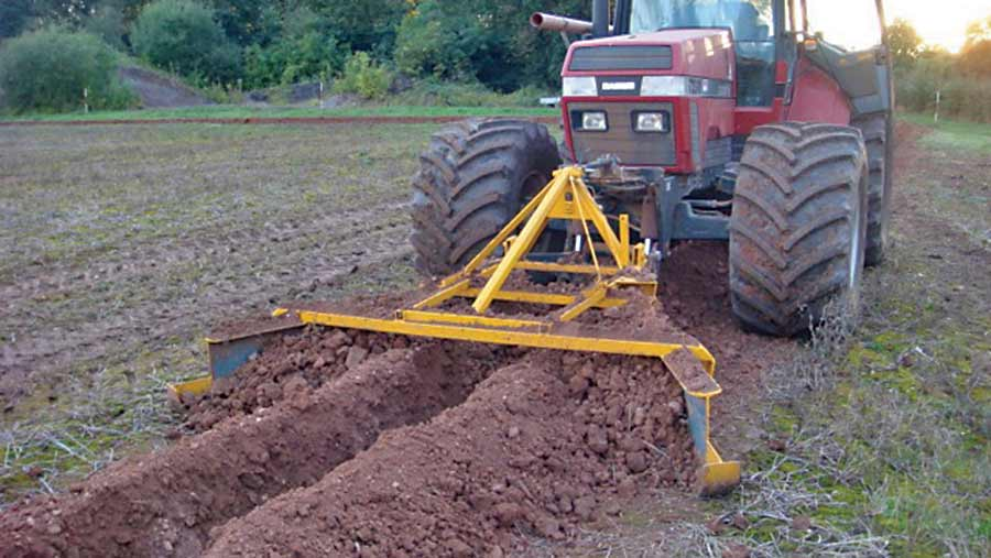 V-shaped trench filler being pushed by a tractor