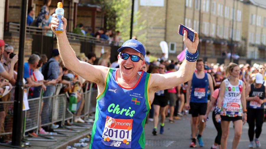 Chris Hewis raises his arms as he runs surrounded by other runners