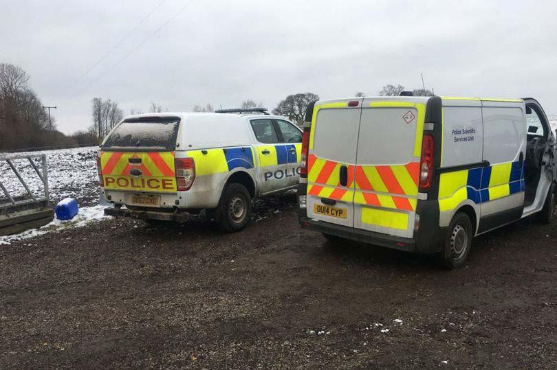 Police vehicles on farm