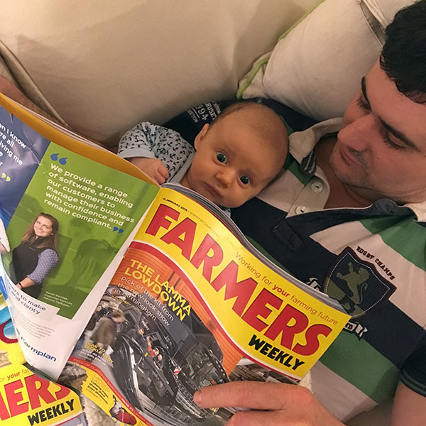 Baby George with Dad Matt reading Farmers Weekly