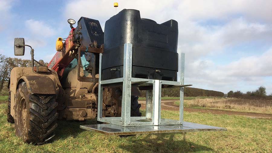 A telehandler moves a black tank with a steel frame
