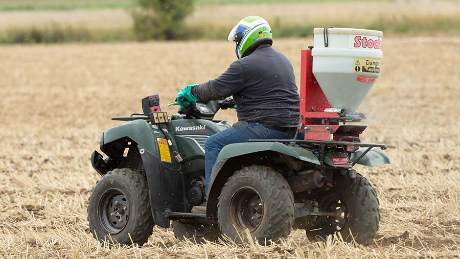 An ATV being operated safely by a driver wearing a helmet