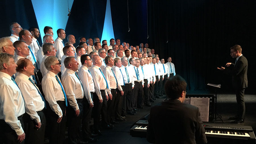 John Wakefield and choir members signing