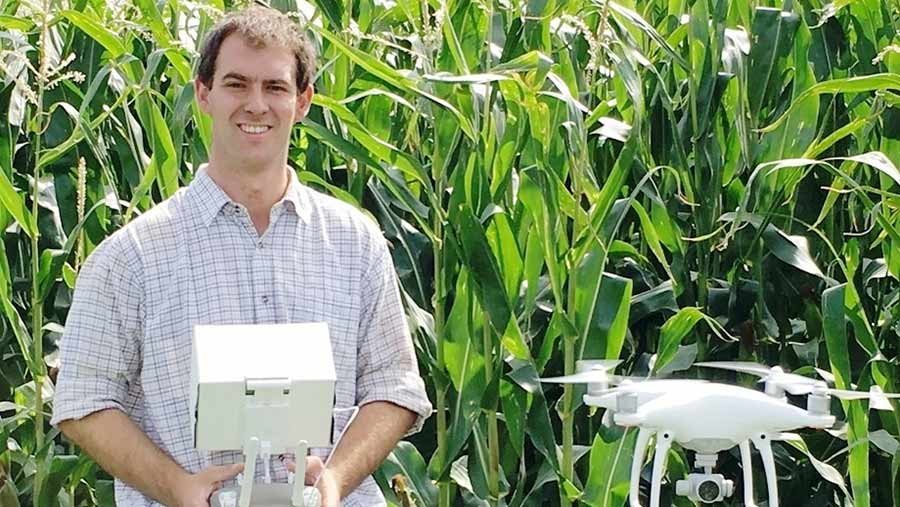 Craig Green holds drone control box with drone hovering beside him