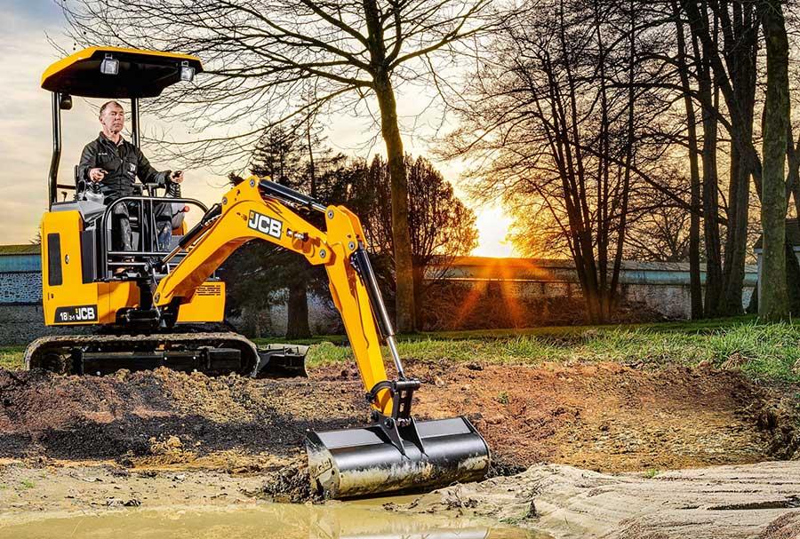 Mini JCB excavator digging on a farm
