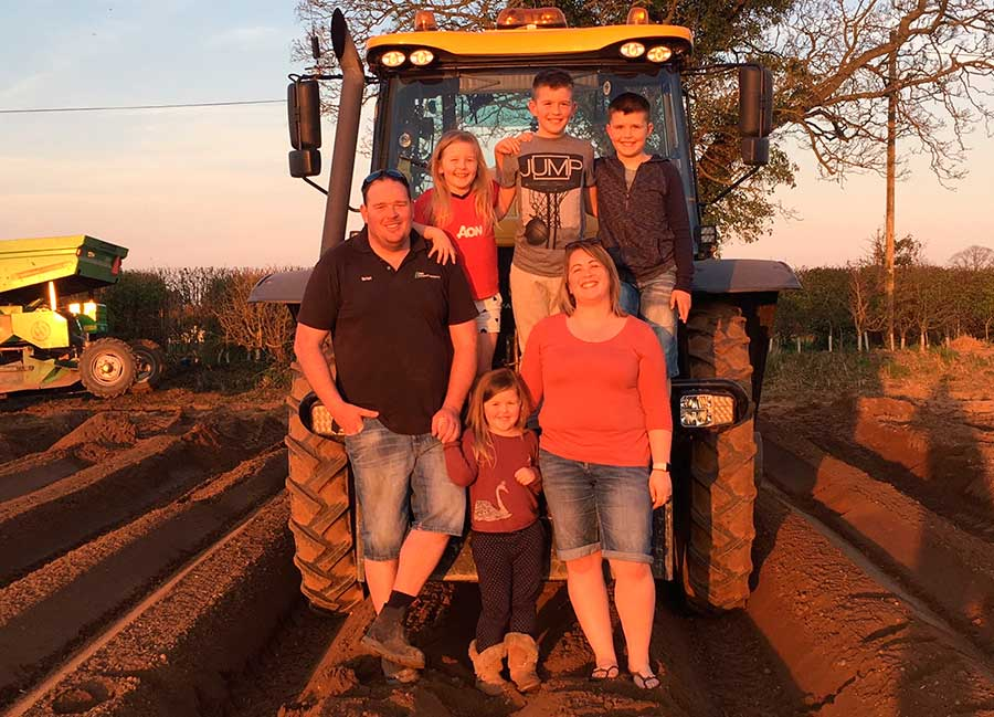 Farmers Brian and Carla May Roberts stand with four children by a tractor