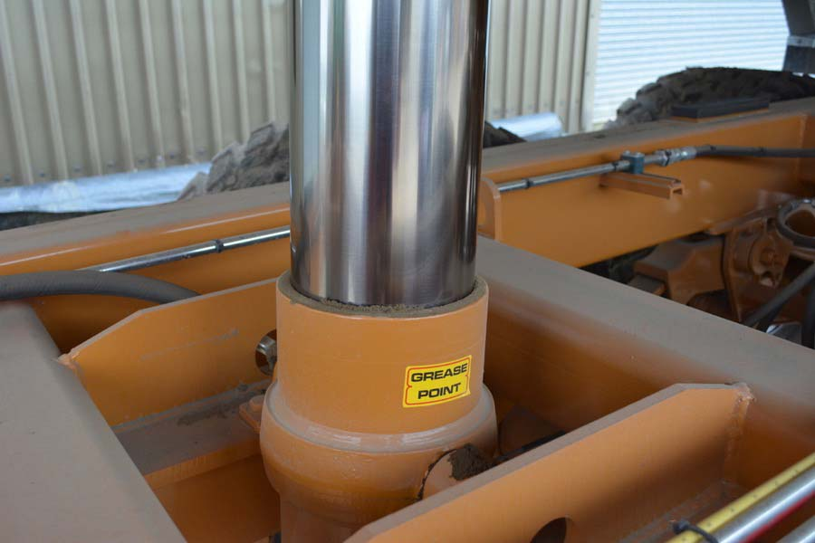 "Shiny hydraulic ram with ""grease point"" label"