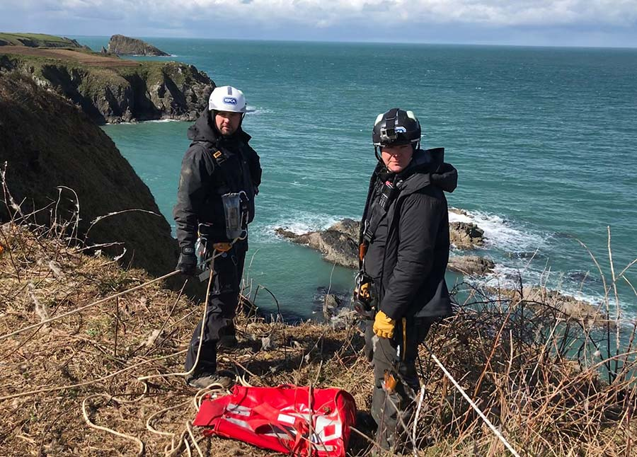 Rescue workers standing on edge of cliff