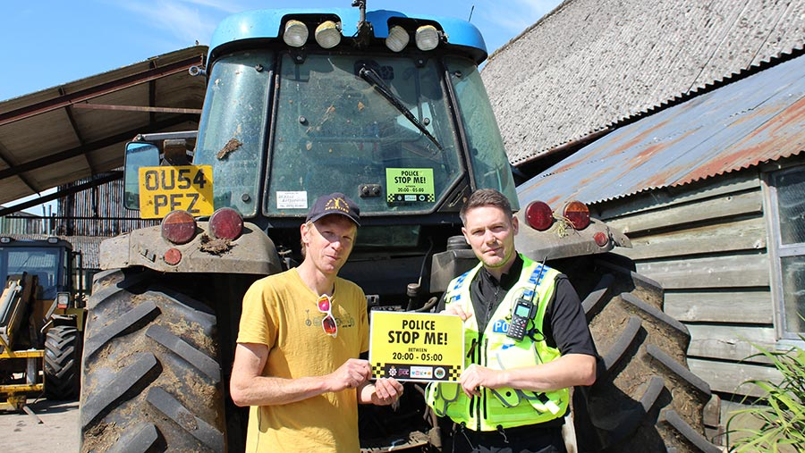 Rural Crime Officer PC Marc Jackson and farmer Andy Rumming apply one of the stickers