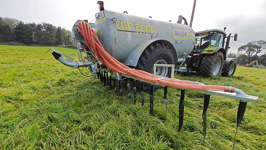 A tractor pulling a slurry tanker with a dribble bar in a field