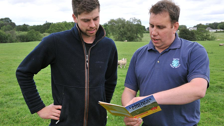 Rob Mitchell and Mark pass reading a booklet in a field