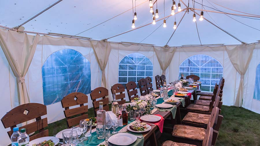Interior of a marquee with a long dining table and chairs