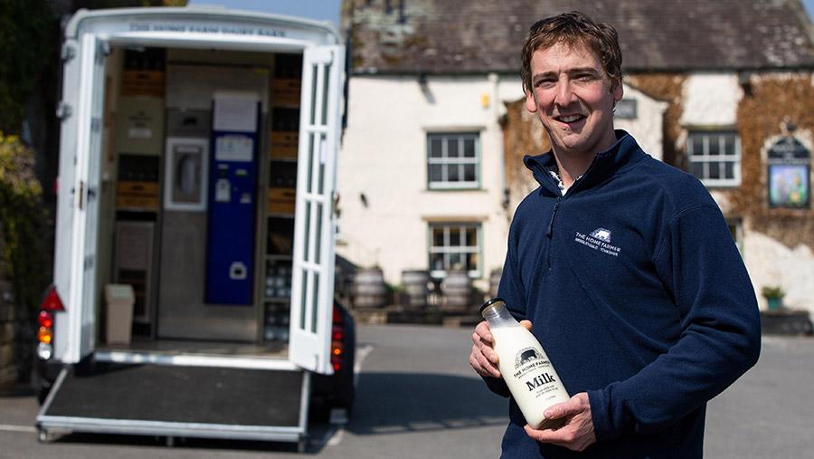 Ben Spence holding milk bottle in front of the mobile vending machine