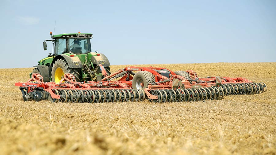 A tractor pulling a cultivator