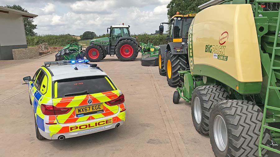 Farm vehicles and a police car on a farmyard