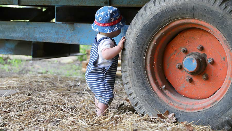 Posed picture of a small child standing by a tractor wheel