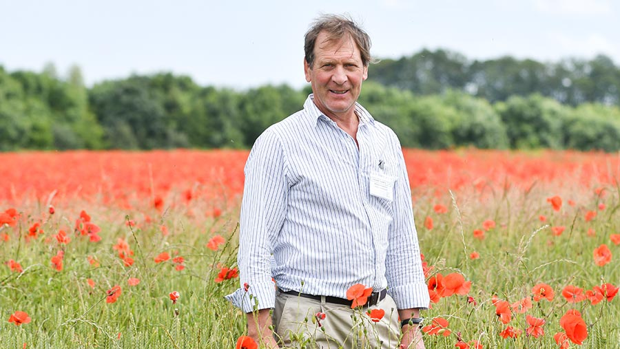 Richard Thompson in a field of barley with poppies