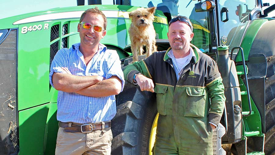 Two men and a dog stand in front of a tractor