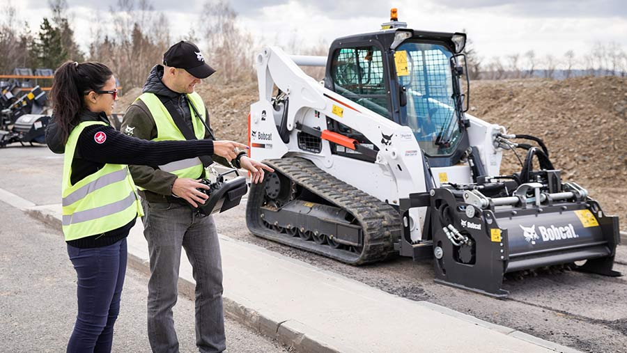 A man and woman using a remote control to control a bobcat