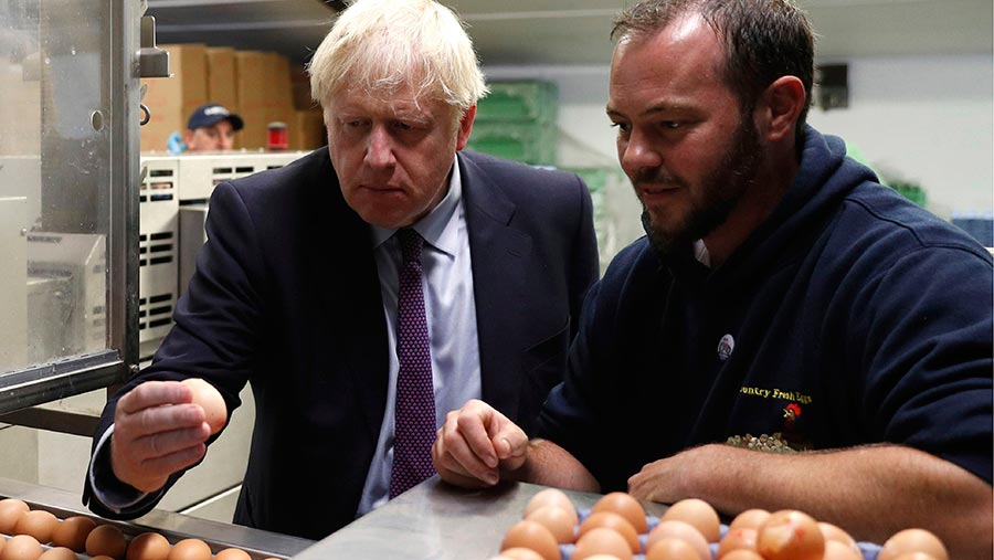 Boris Johnson inspects eggs with farmer Matt Shervington-Jones yesterday during his visit to Wales © Adrian Dennis/AP/Shutterstock