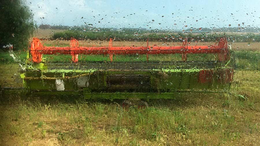 Combine seen through a wet car window