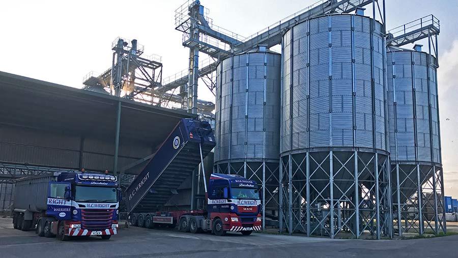 Grain silos and two trucks at grain store