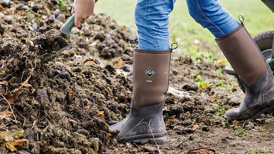 A farmer shovelling muck in welly boots