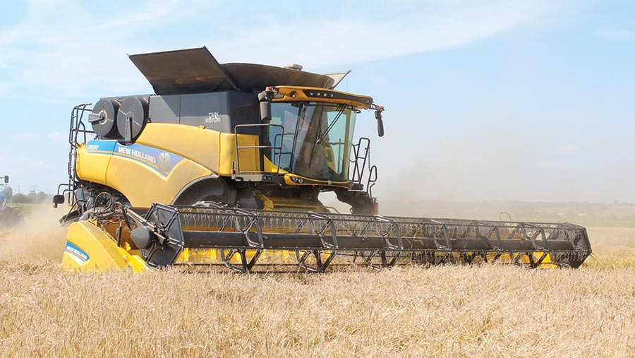 a yellow combine harvester cutting a crop
