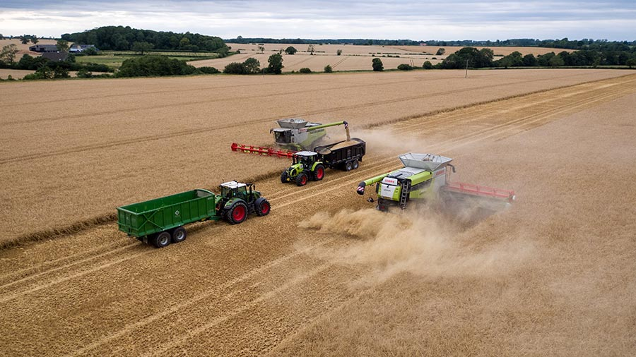 Two combines and two tractors harvesting by Freddie Gittus