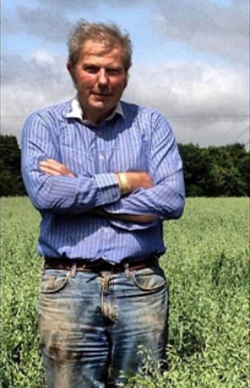 William Taylor standing with his arms crossed in a field