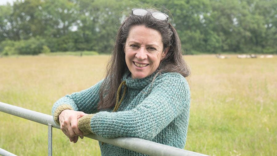 Emma Boyles standing by farm fence