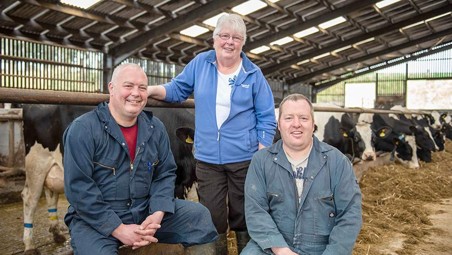 John, Margaret and Stuart Harvey in a cow shed